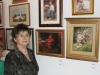 Krysia Bujnowicz (Kanwa) poważna i skupiona pozuje na tle przepięknych obrazów.
